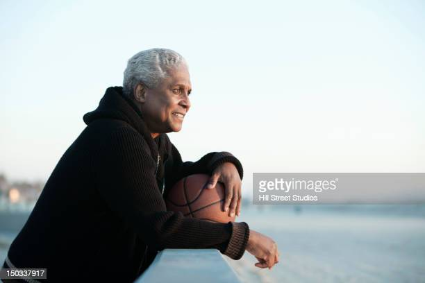 Black man standing outdoors with basketball