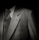 Black & White film photo of man suit detail against black background. Low key exposure to give it a sinister semblance.