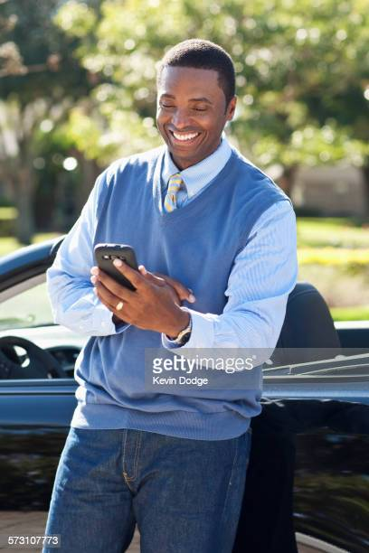 Black man using cell phone at convertible