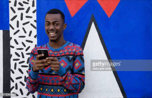 Black man using cell phone near colorful wall