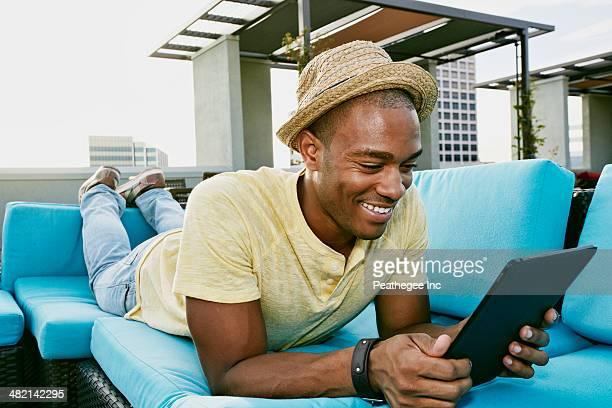 Black man using digital tablet on sofa on urban rooftop