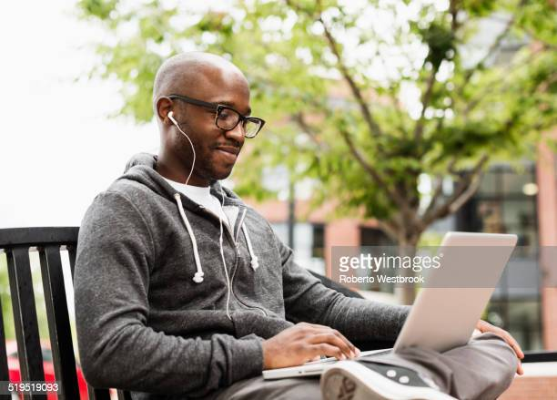 Black man using laptop and earphones on city bench