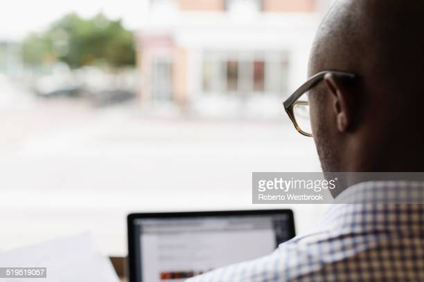 Black man using laptop at window