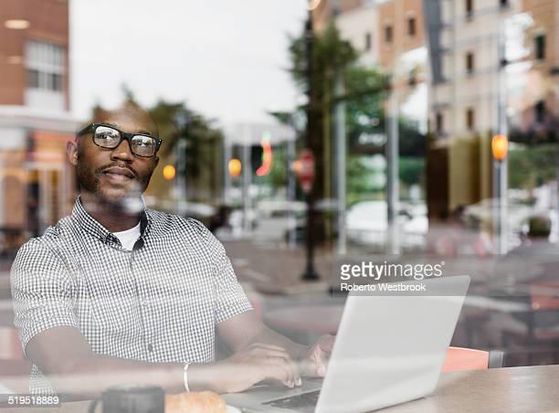Black man using laptop in coffee shop