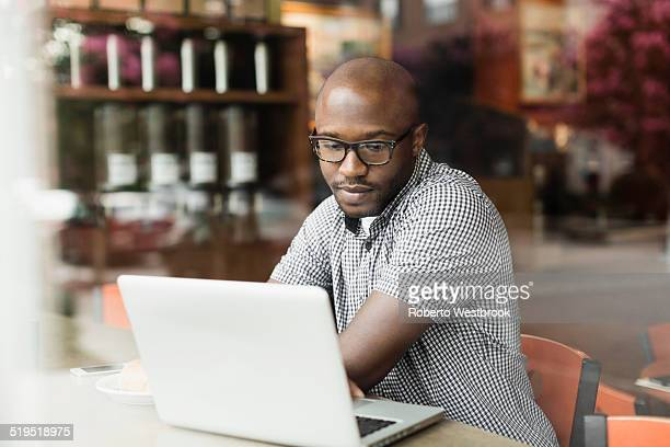 Black man using laptop in coffee shop