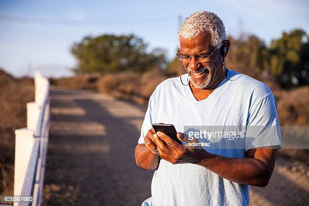 Black Man using smartphone on mountain trail