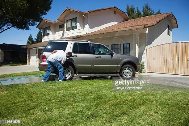 Black man washing car in driveway