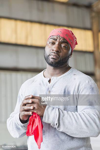 Black man wearing do rag and grimy shirt