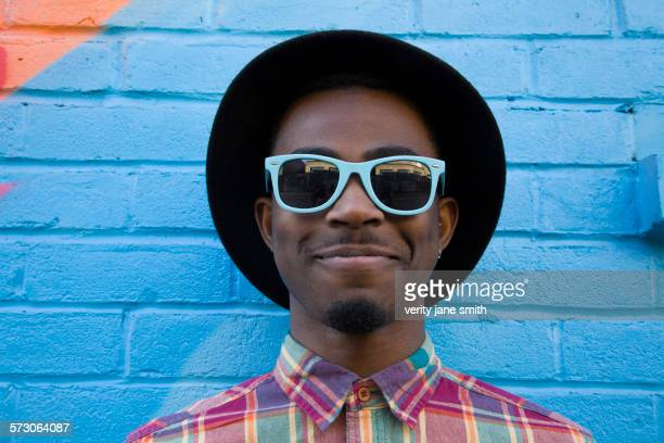 Black man wearing sunglasses near colorful wall