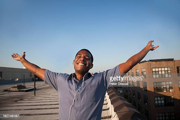 Black man with arms outstretched on rooftop