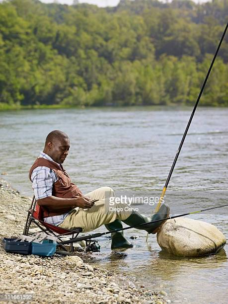Black man with cell phone fishing in stream
