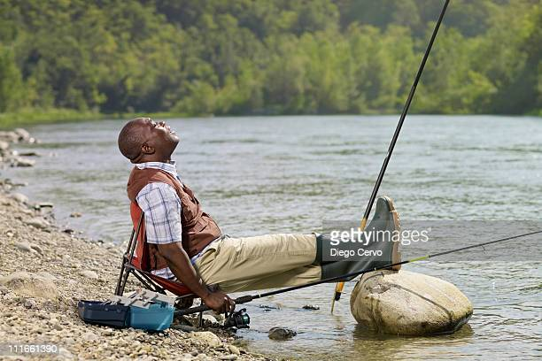 Black man with feet up fishing in stream