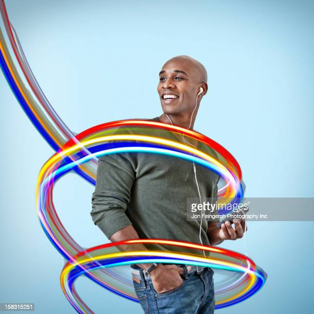 Black man with mp3 player surrounded by colorful lines