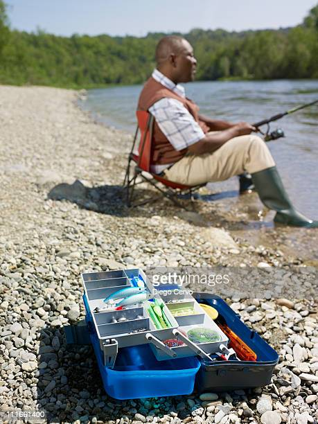 Black man with tackle box fishing in stream