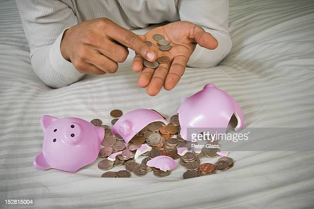 Black man with US coins and broken piggy bank