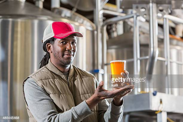 Black man working in a small brewery holding beer