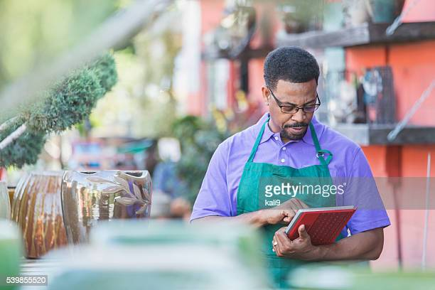 Black man working in garden center using digital tablet