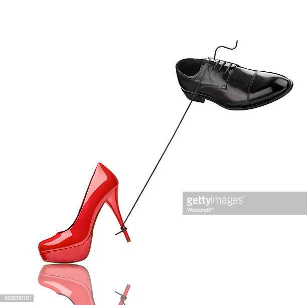 Black mans shoe and red high heel in front of white background