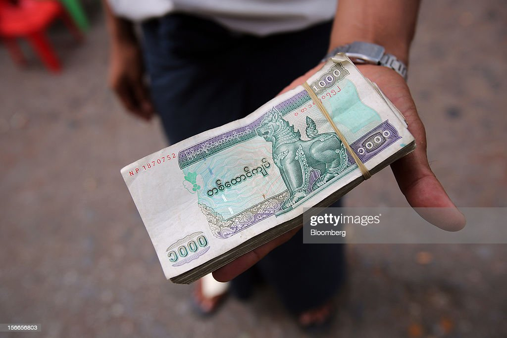 A black market currency exchange seller holds a stack of 1000 Kyat banknotes at a market in Yangon, Myanmar, on Sunday, Nov. 18, 2012. President Barack Obama will become the first sitting U.S. president to visit Myanmar when he travels to Yangon on Nov. 19 to meet President Thein Sein and Aung San Suu Kyi, the opposition leader who spent more than 15 years under house arrest before the country shifted to democracy after decades of military rule. Photographer: Dario Pignatelli/Bloomberg via Getty Images