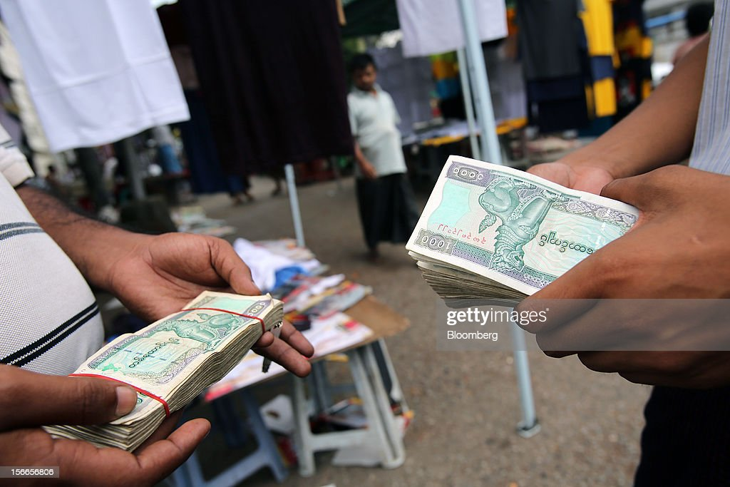 Black market currency exchange sellers hold stacks of 1000 Kyat banknotes at a market in Yangon, Myanmar, on Sunday, Nov. 18, 2012. President Barack Obama will become the first sitting U.S. president to visit Myanmar when he travels to Yangon on Nov. 19 to meet President Thein Sein and Aung San Suu Kyi, the opposition leader who spent more than 15 years under house arrest before the country shifted to democracy after decades of military rule. Photographer: Dario Pignatelli/Bloomberg via Getty Images