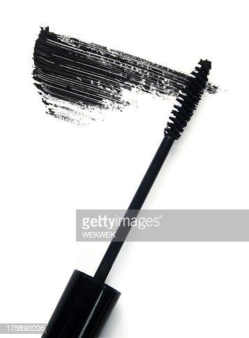 Black mascara brush and smear of mascara on white background