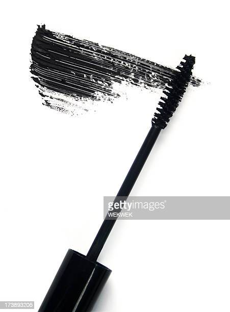 Black mascara brush and smear of mascara on white background