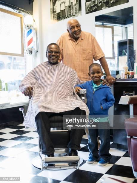 Black men and grandson smiling in retro barbershop