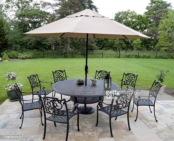 Black metal patio furniture set with tan umbrella