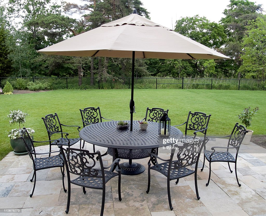 Black Metal Patio Furniture Set With Tan Umbrella : Stock Photo