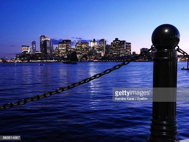 Black Metallic Bollard With Chain Against Illuminated Cityscape