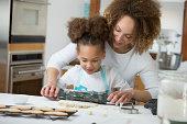 Black mother and daughter baking together