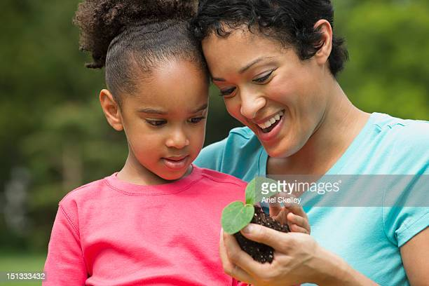Black mother and daughter gardening
