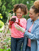 Black mother and daughter gardening together