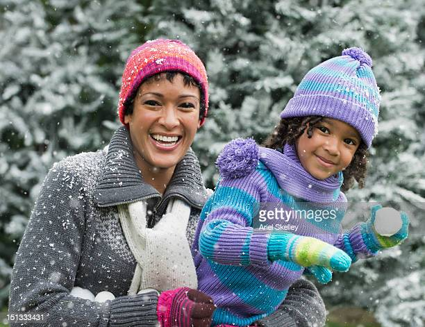 Black mother and daughter having a snowball fight