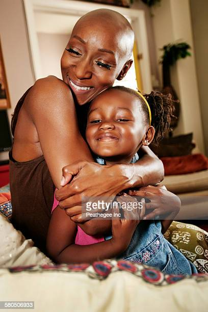Black mother and daughter hugging on sofa