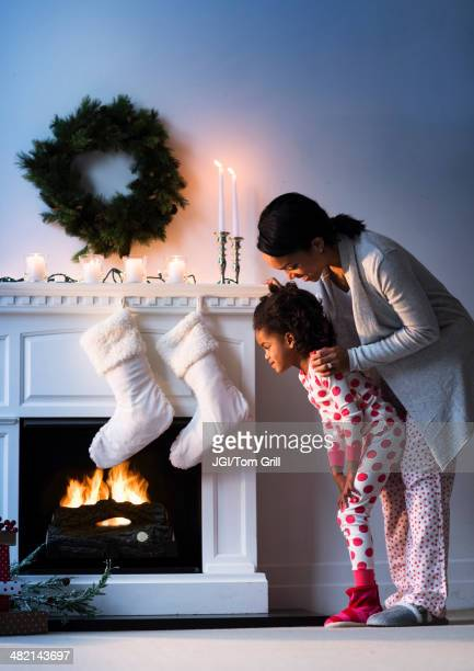 Black mother and daughter looking at Christmas stockings