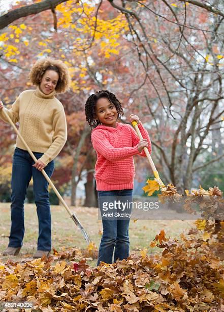 Black mother and daughter raking autumn leaves
