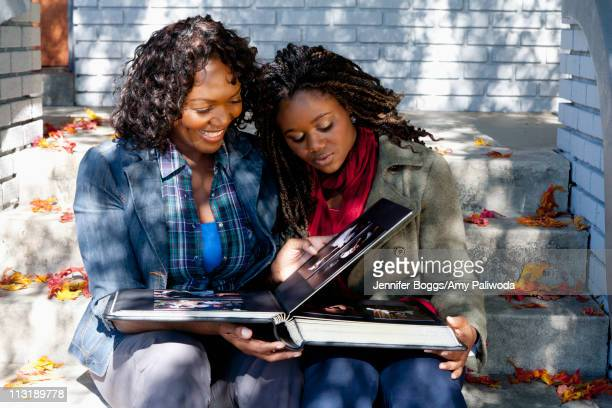 Black mother and daughter sitting on front stoop looking at photo album