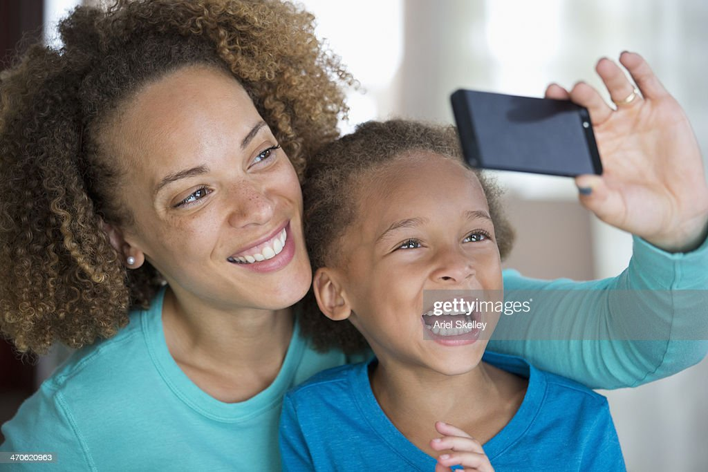 Black mother and daughter using cell phone : Stock Photo