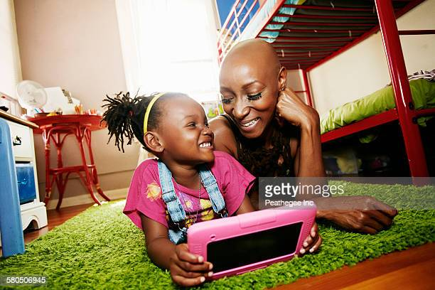 Black mother and daughter using digital tablet in bedroom