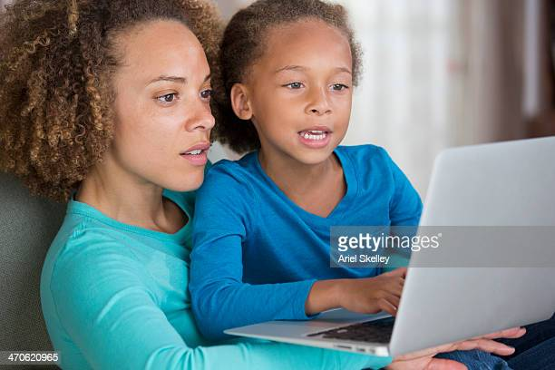 Black mother and daughter using laptop