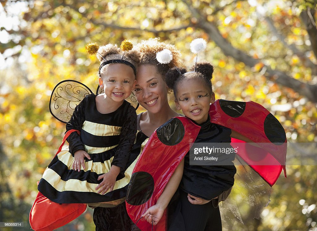 Black mother and daughters in Halloween costumes : Stock Photo