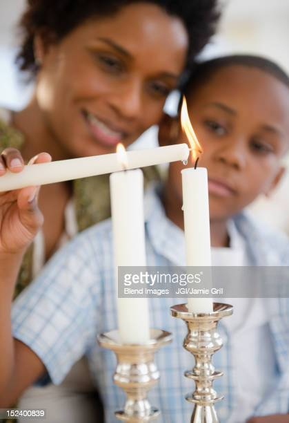 Black mother and son lighting candles together