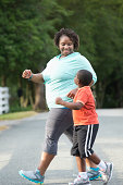 Black mother and son walking on road