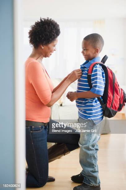 Black mother buttoning son's shirt