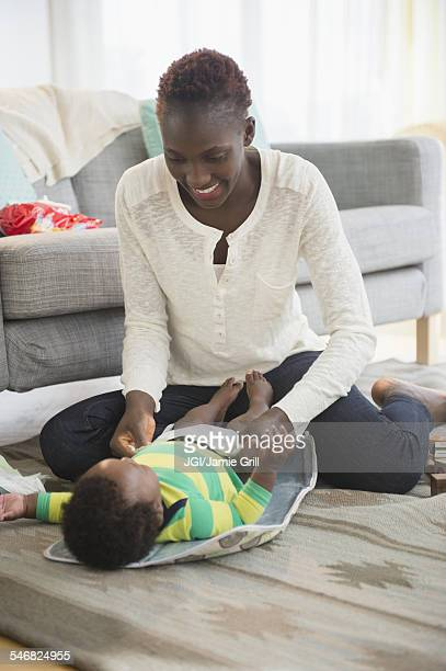 Black mother changing diaper of baby boy in living room