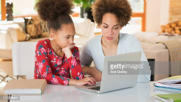 Black mother helping daughter with homework on laptop