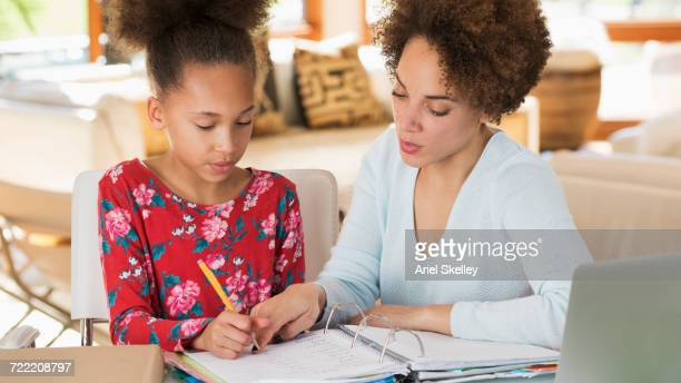 Black mother helping daughter with homework