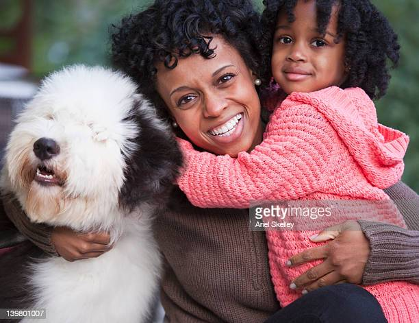 Black mother hugging daughter and dog outdoors