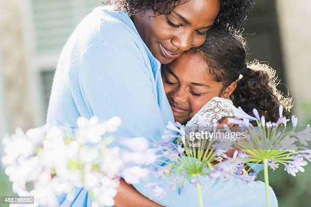 Black mother hugging daughter outdoors with flowers